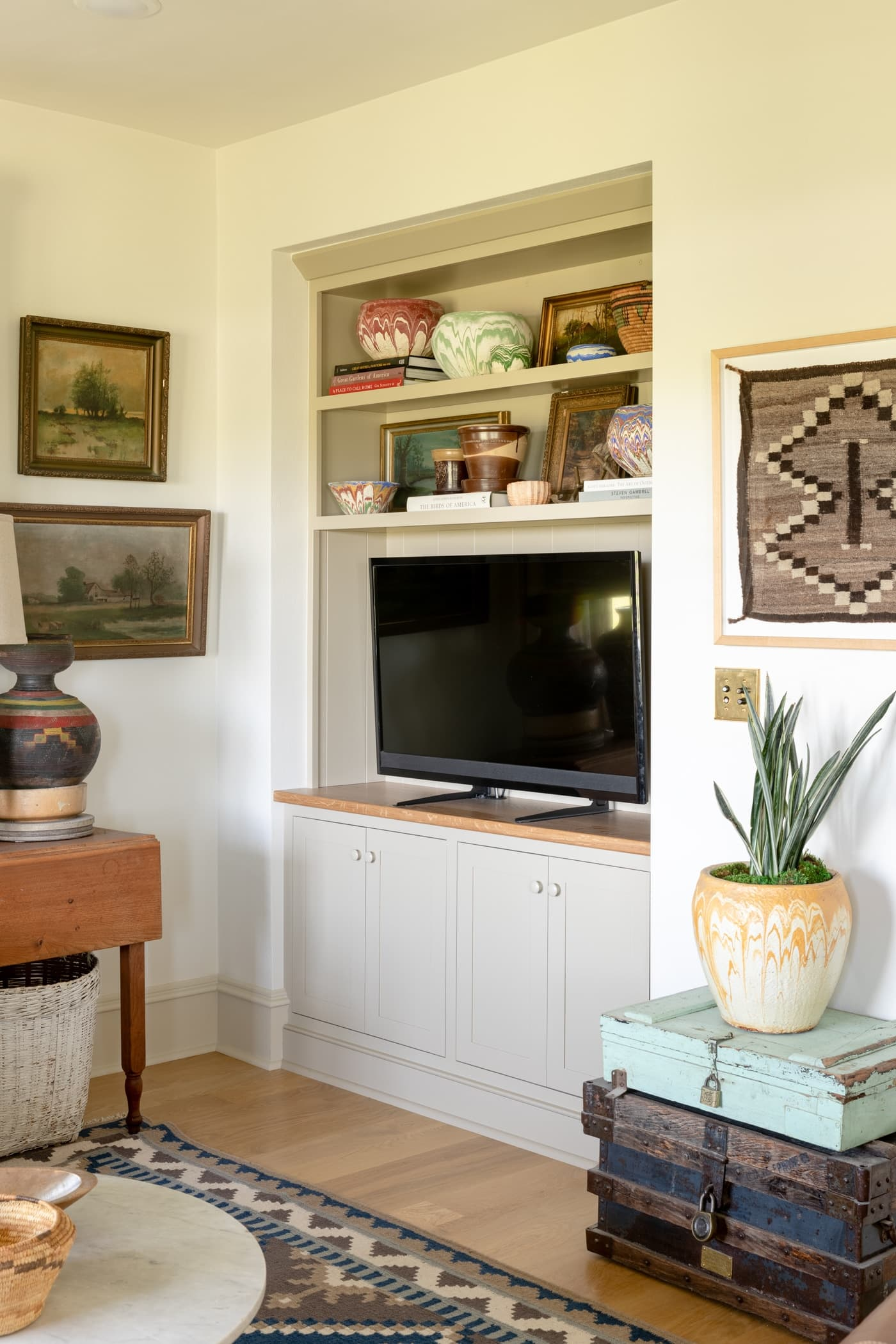 TV sitting in a built-in unit with cabinets underneath and shelves above with paintings on the surrounding walls and a blue rug on on the hardwood floors