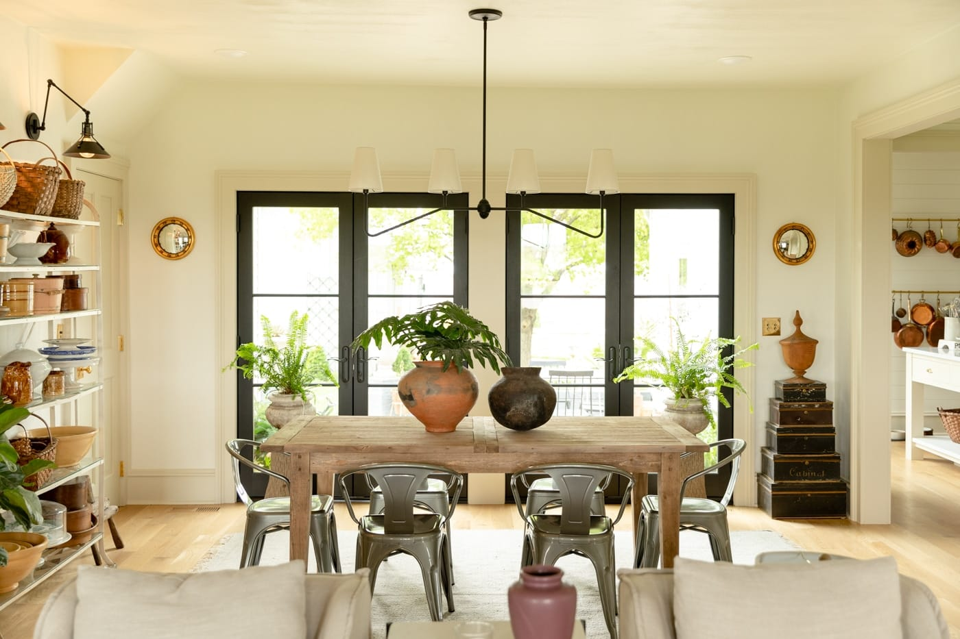 Wood dining room table with metal chairs around with pots and plants on table and large French doors in background