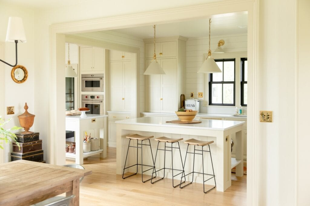 Creamy and light farmhouse kitchen with large island and three stool tucked away with wall oven and black windows