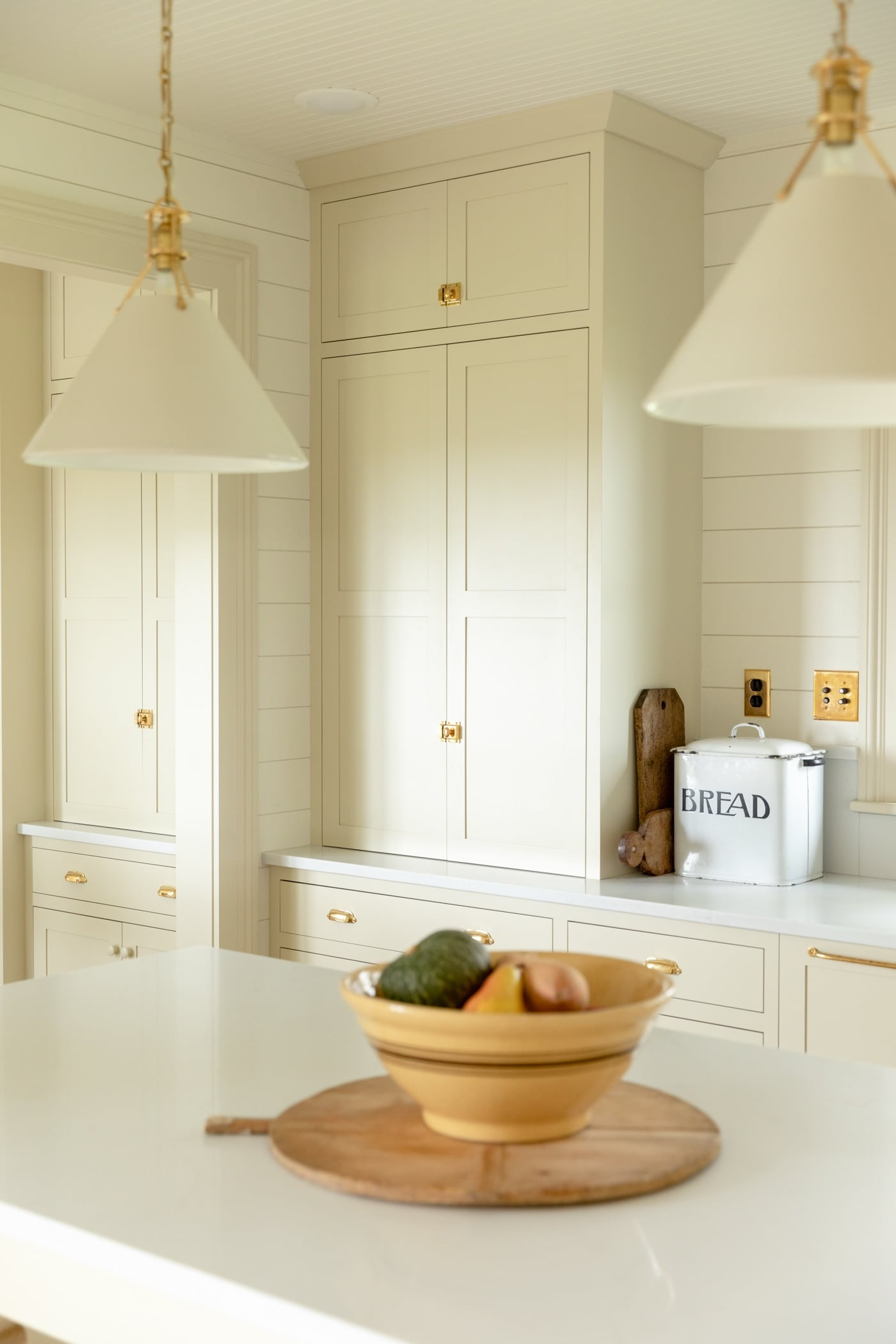 Large pantry cabinet in creamy white farmhouse kitchen with yellow bowl filled with squash sitting on large island with white countertop and pendants hanging above island