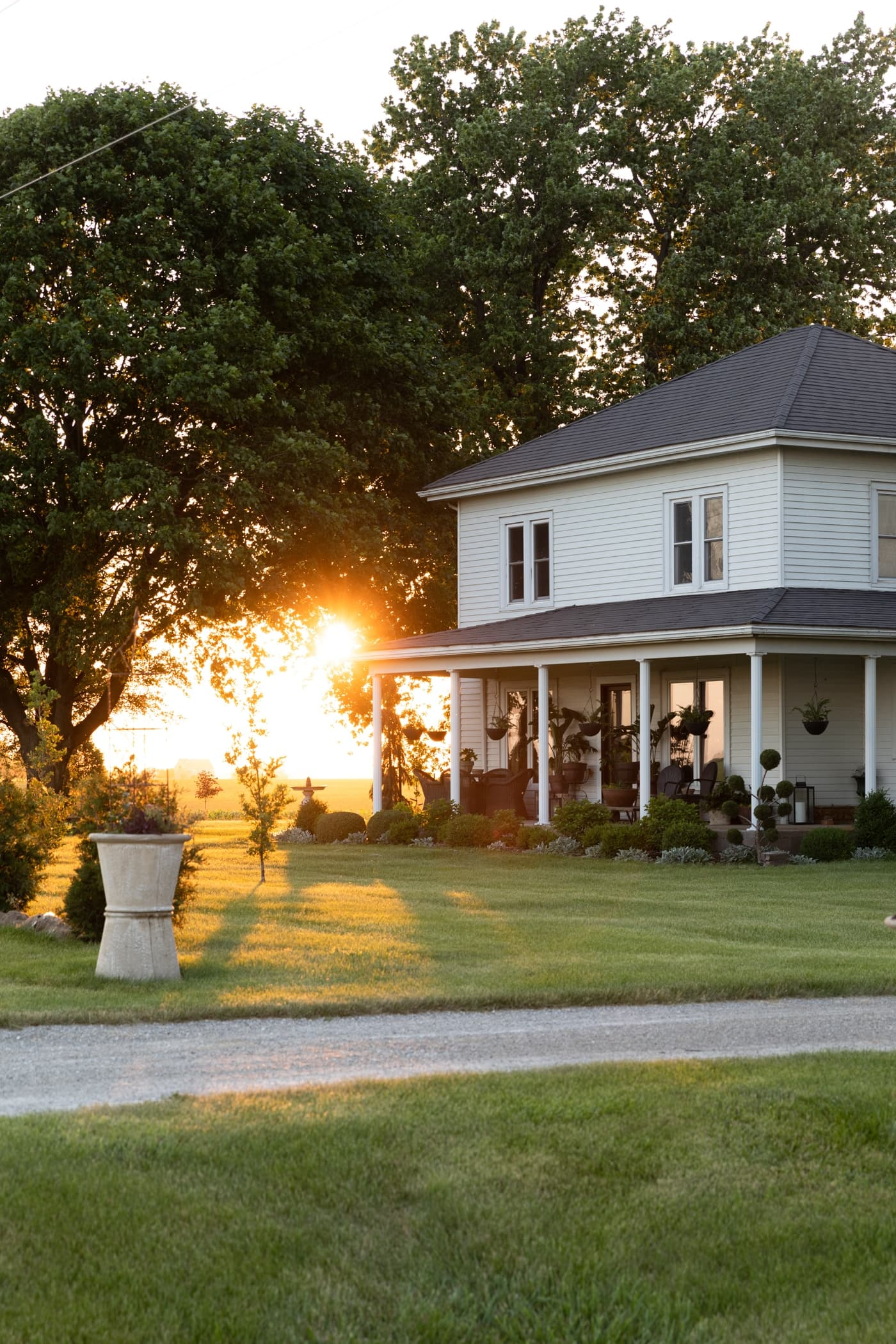 Exterior of white farmhouse with large front door and double windows with sun setting in background
