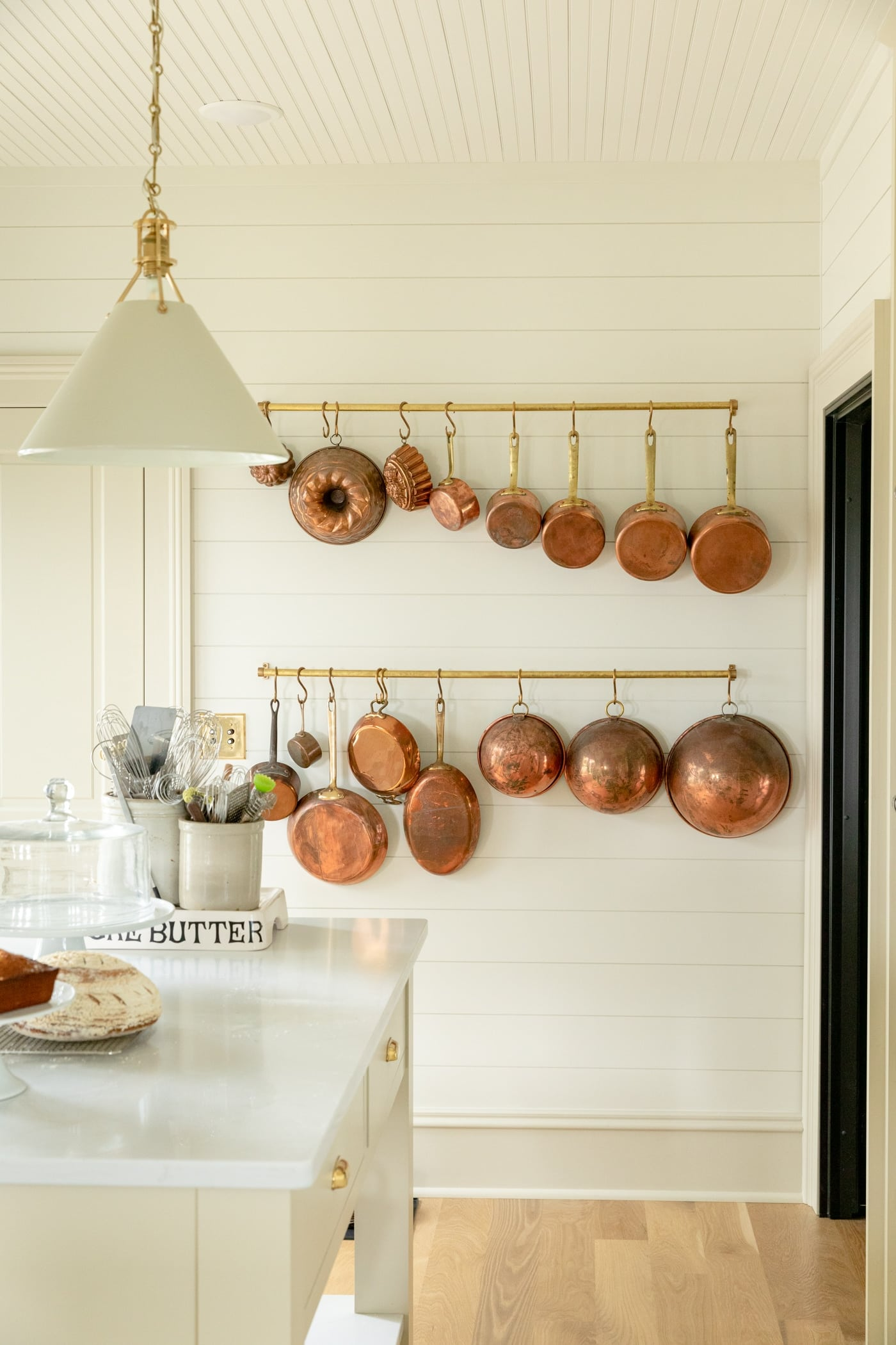 Lots of copper pots hanging on a brass rail with ship lap and large baseboard all with light wood floors