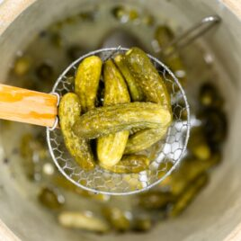 Top down view of yellow and green colored pickles sitting in a wire spider on top of a large crock holding other pickles