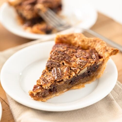 Slice of pecan pie with chocolate layer on bottom sitting on white plate with napkin underneath with half eaten piece of pie in background all on wooden surface