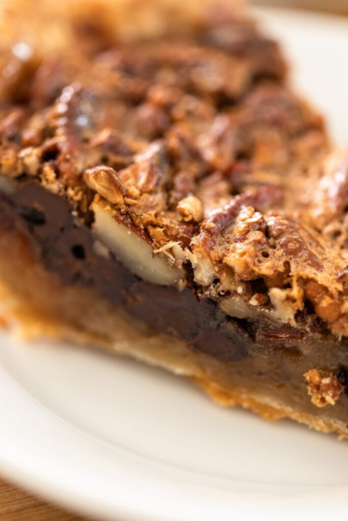 Close up view of side of piece of pecan pie showing chocolate layer along bottom with pie sitting on white plate