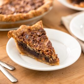 Piece of chocolate bourbon pecan pie with golden crust sitting on white plate with forks beside with extra pieces of pie sitting in background along with rest of pie all on brown wooden surface