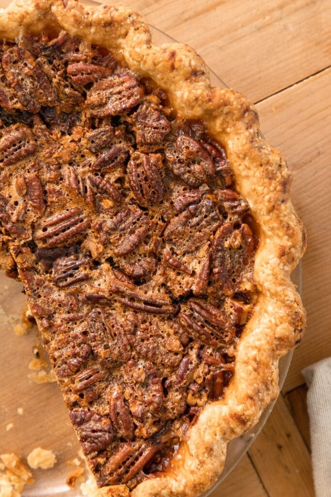 Top down view of pecan pie sitting in pie dish with pecans all over the top sitting on wood surface