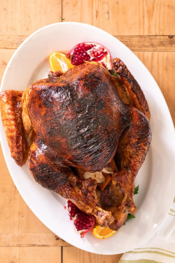 Top down view of a cooked turkey with browned skin sitting on a white platter with orange and pomegranate all on wood board