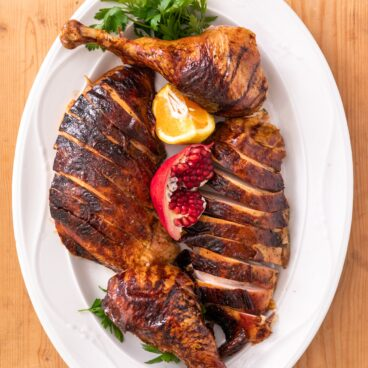 Top down view of citrus dry-brine turkey pieces sitting on white serving platter with pomegranate and orange slice all on wood board