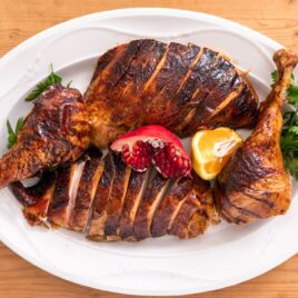 Top down view of brown-skinned pieces of turkey on white serving platter with pomegranate and slice of orange and parsley all on wood board