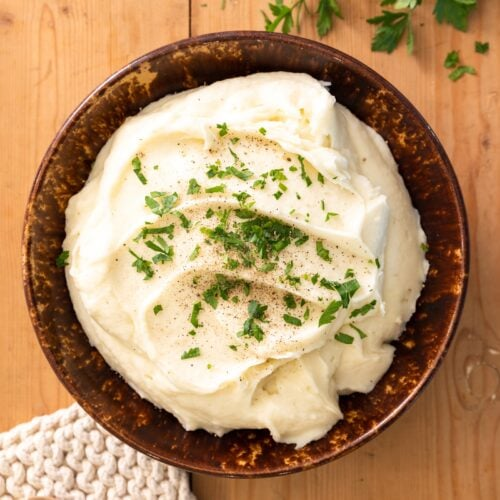Top down view of creamy white mashed potatoes sitting in brown bowl topped with green parsley with extra parsley in background all on wood board