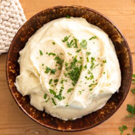 Top down view of brown bowl filled with mashed potatoes topped with green parsley with hot pad and wooden spoon