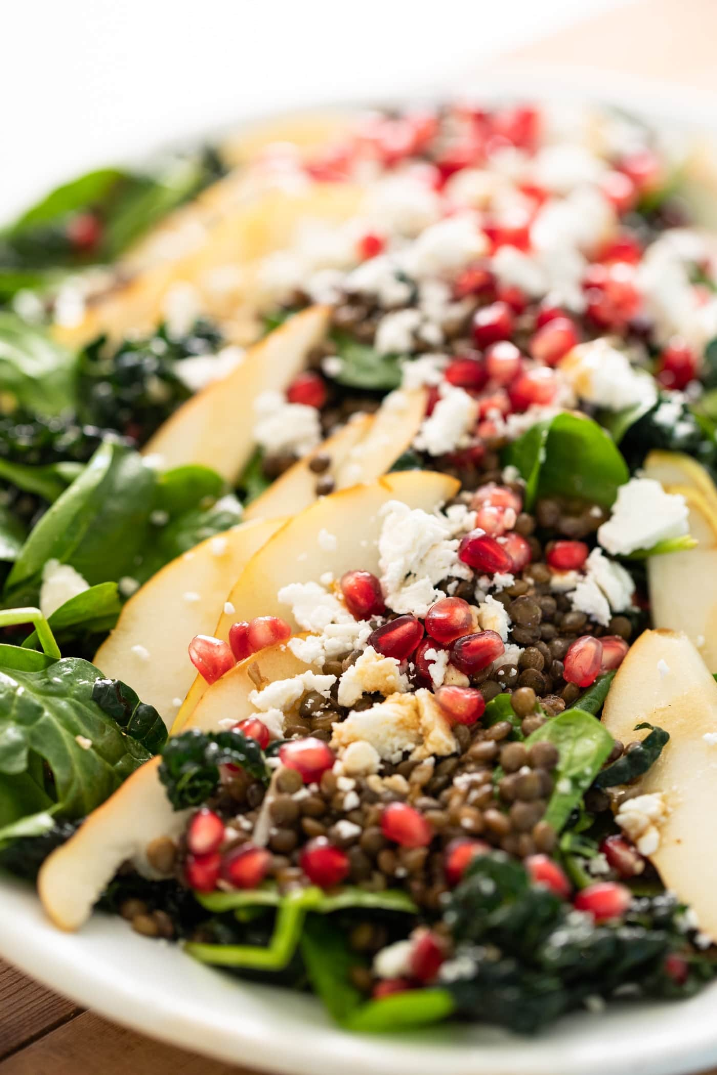 Close view of big slices of pear laying on top of green kale and spinach and topped with pomegranate seeds and white crumbles of feta cheese
