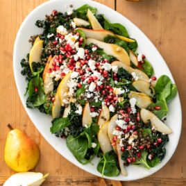 Top down view of large white platter filled with kale and spinach leaves and topped with pears, lentils, pomegranate arils, and crumbles of white feta cheese