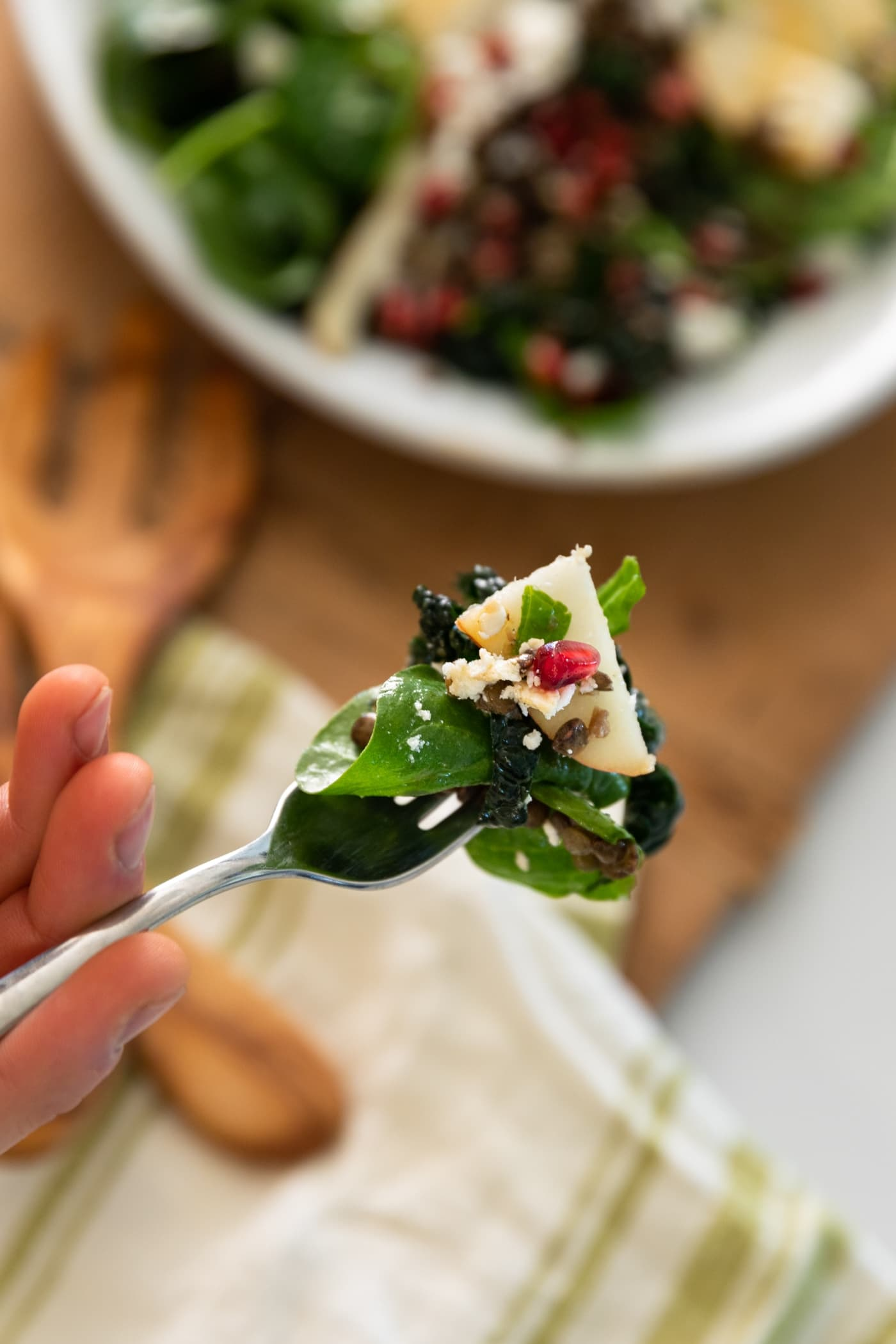 Fork holding bite of salad topped with pomegranate aril and white feta cheese with rest of salad in background