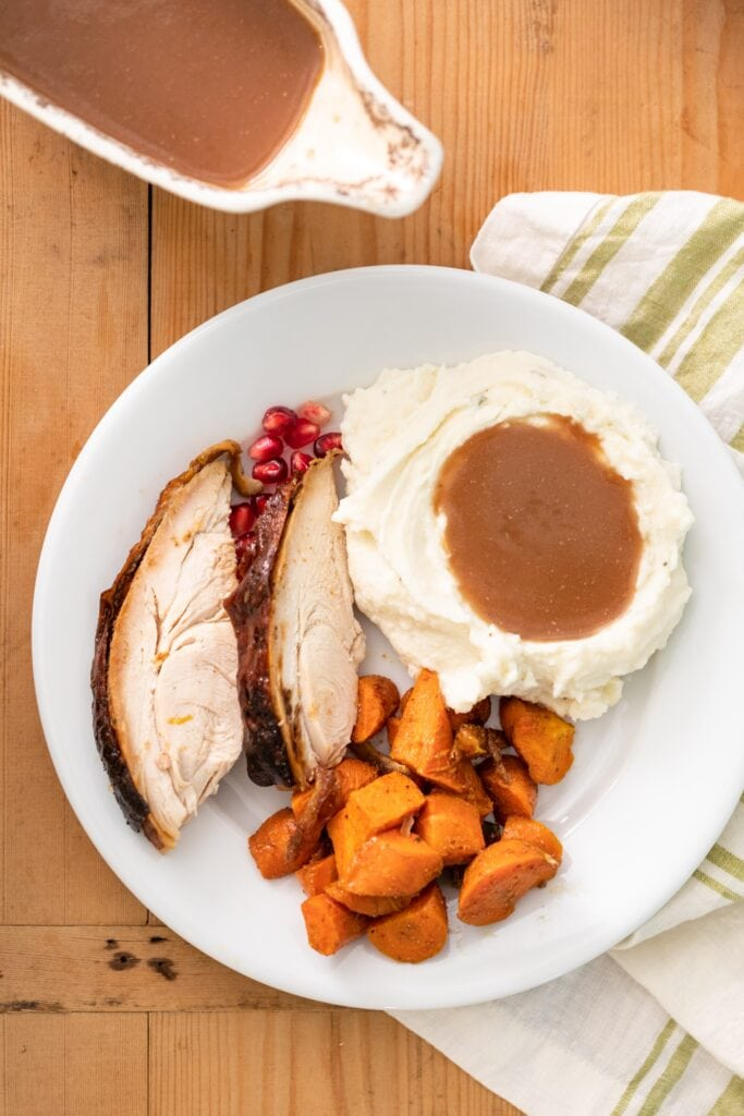 Top down view of plate filled with Thanksgiving dishes including white mashed potatoes topped with homemade gravy with extra gravy in white container to the side all on wood surface