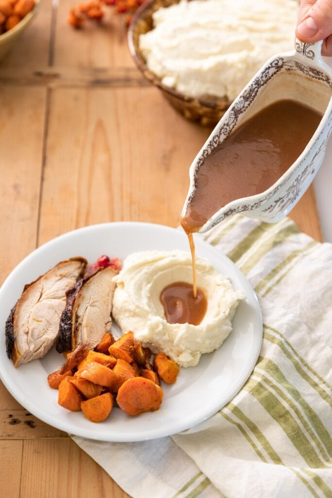 Brown colored homemade gravy being poured out of a white gravy boat onto a pile of white mashed potatoes sitting one plate with other holiday side dishes and turkey all on wood surface