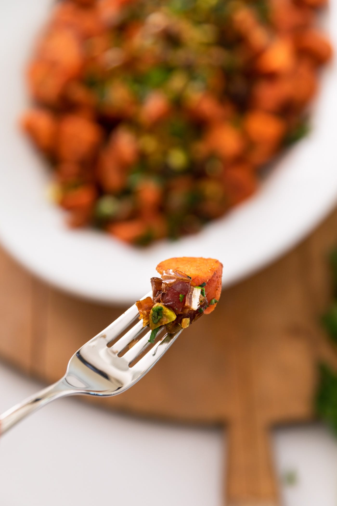 Fork holding carrot and piece of date in front of bowl filled with carrots and wood cutting board