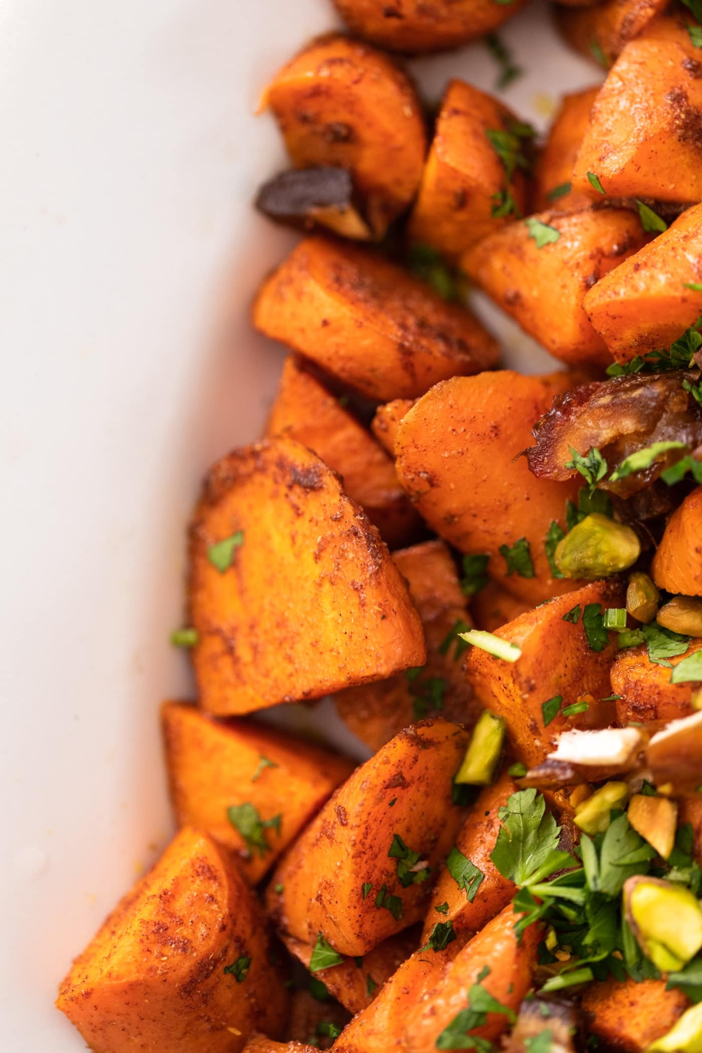 Orange carrots tossed in spice blend with brown flakes sitting in white bowl with bits of dates and carrots on top