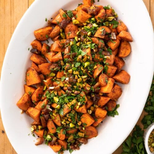 Top down view of orange roasted carrots sitting in white serving platter topped with dates and pistachios all on a wood surface with extra parsley