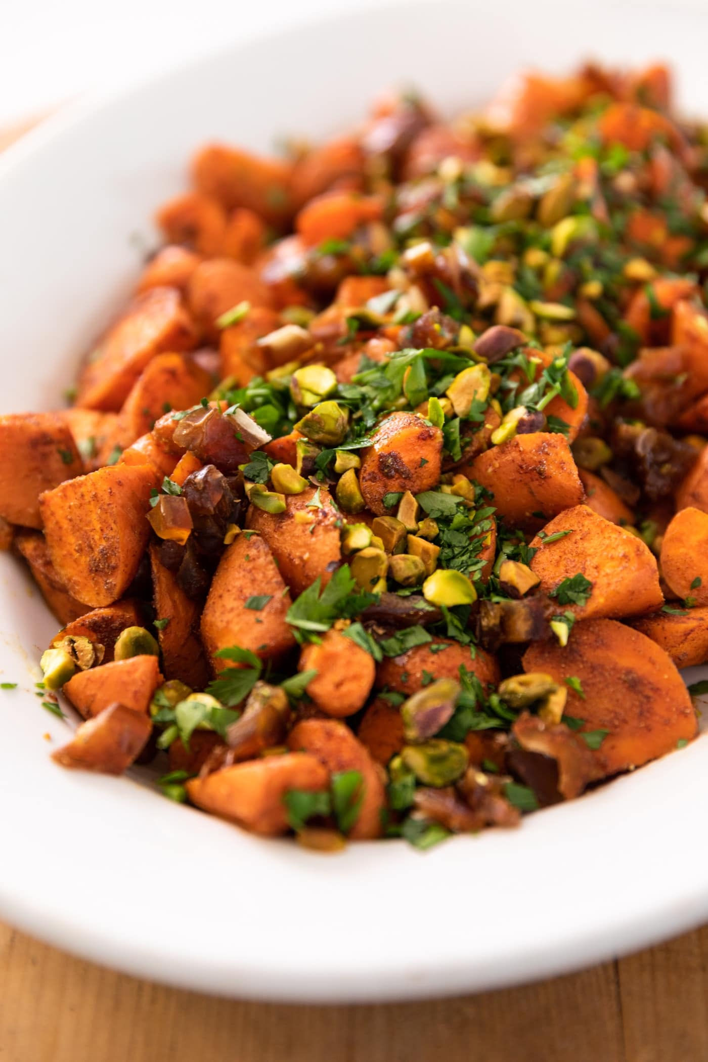 Roasted carrots piled into a white serving bowl topped with parsley, pistachios, and dates