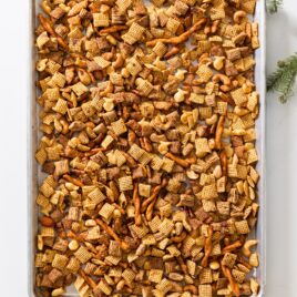 Top down view of baking sheet sitting on white surface filled with browned pieces of cereal after coming out of the oven