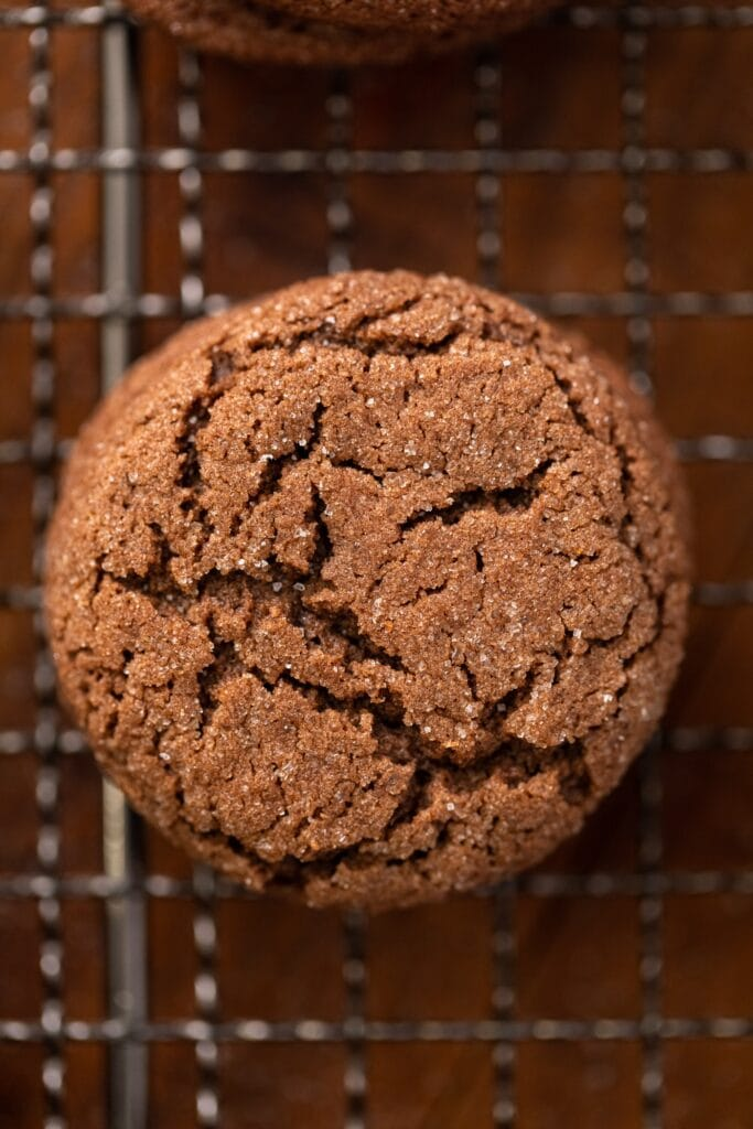Top down close up view of top of chocolate cookie with cracks and sugar sprinkled on top sitting on wire cooling rack on wood surface