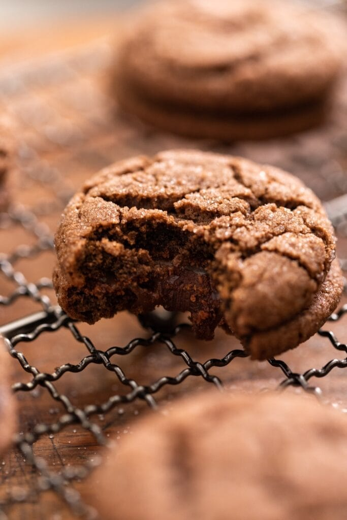 Chocolate cookie with bite taken out showing inside with gooey chocolate filling sitting on cooling rack with other chocolate cookies all around