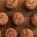 Top down view of brown colored cookies with cracks on the top sprinkled with white sugar and sitting on cooling rack on wood surface