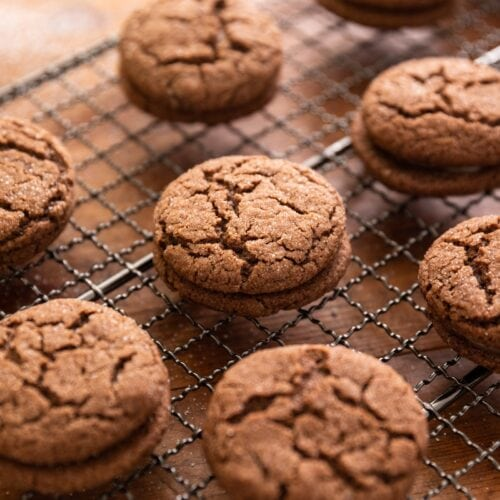 Side view of multiple chocolate thin mint sandwich cookies sitting on cooling rack all on wood surface