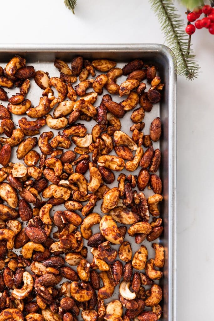 Top down view of cinnamon spiced nuts sitting on silver baking pan on white countertop with Christmas greenery and red berries to the side