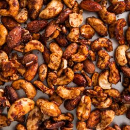 Top down of cinnamon spiced nuts sitting on silver baking pan after coming out of the oven