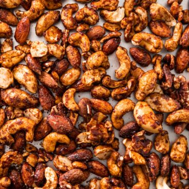 Top down view of spiced nuts sitting on silver baking dish after cooling from being in the oven