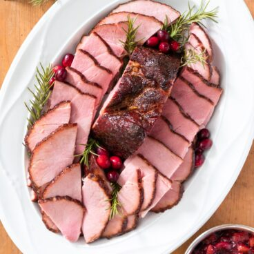 Top down view of pink pieces of ham sliced and placed on white serving platter with sprigs of rosemary around along with silver container filled with red chutney