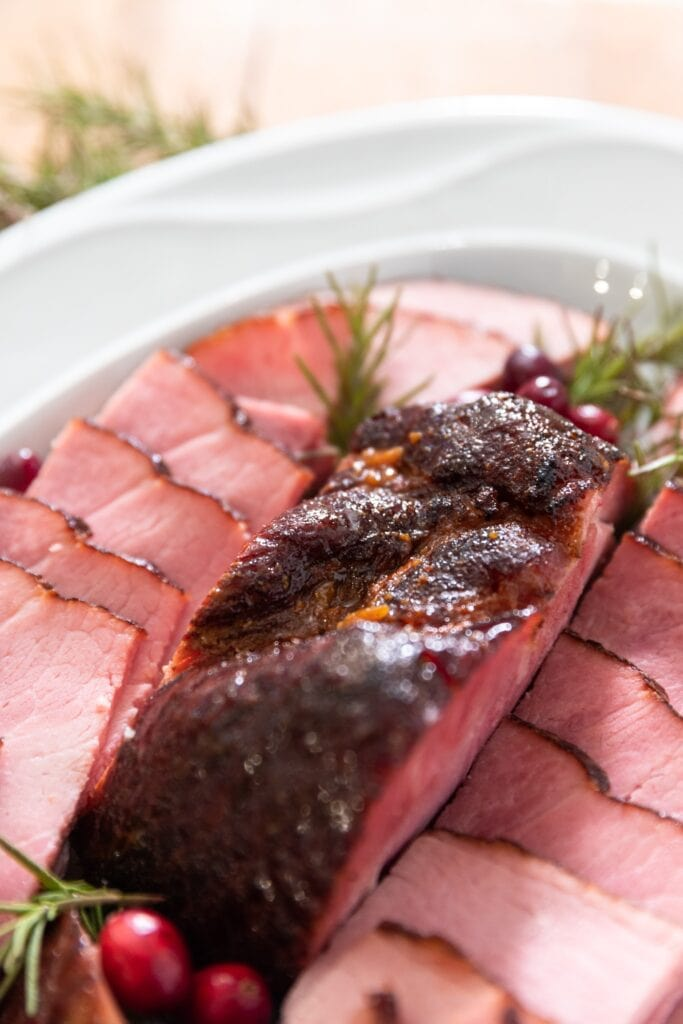 Piece of ham sitting on white platter surrounded by slices of ham along with sprigs of rosemary and red cranberries