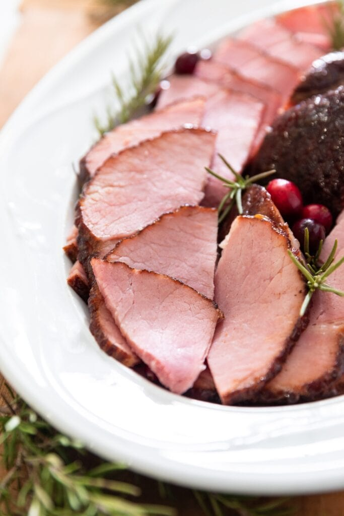 Slices of ham sitting on white platter surrounded by cranberries and sprigs of rosemary all on wood surface