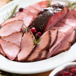 White platter filled with slices of ham along with cranberries and sprigs of rosemary all on wooden board