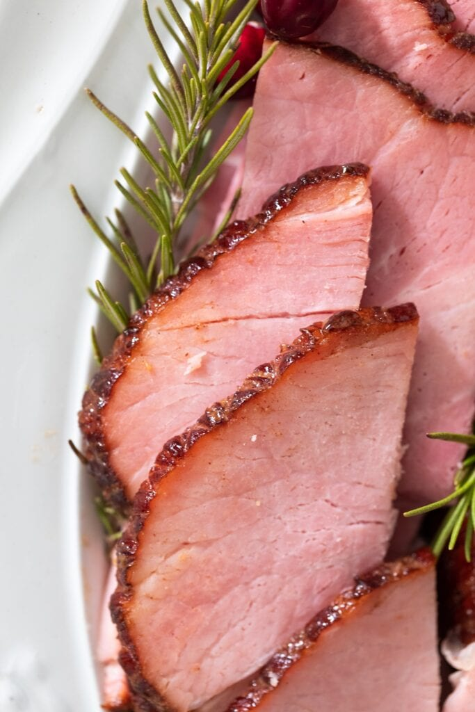Slices of pink ham sitting on white platter with crispy glaze around edges amidst pieces of rosemary and cranberries