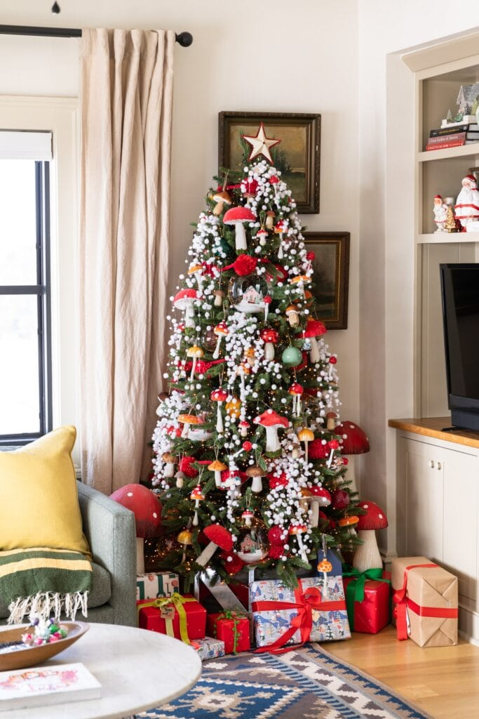 Large Christmas tree packed with red colored mushrooms and snow garland surrounded by presents on the floor and TV cabinet beside
