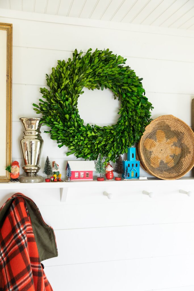 Shelf holding small Christmas ornaments along with green boxwood wreath, bowl, and picture frame