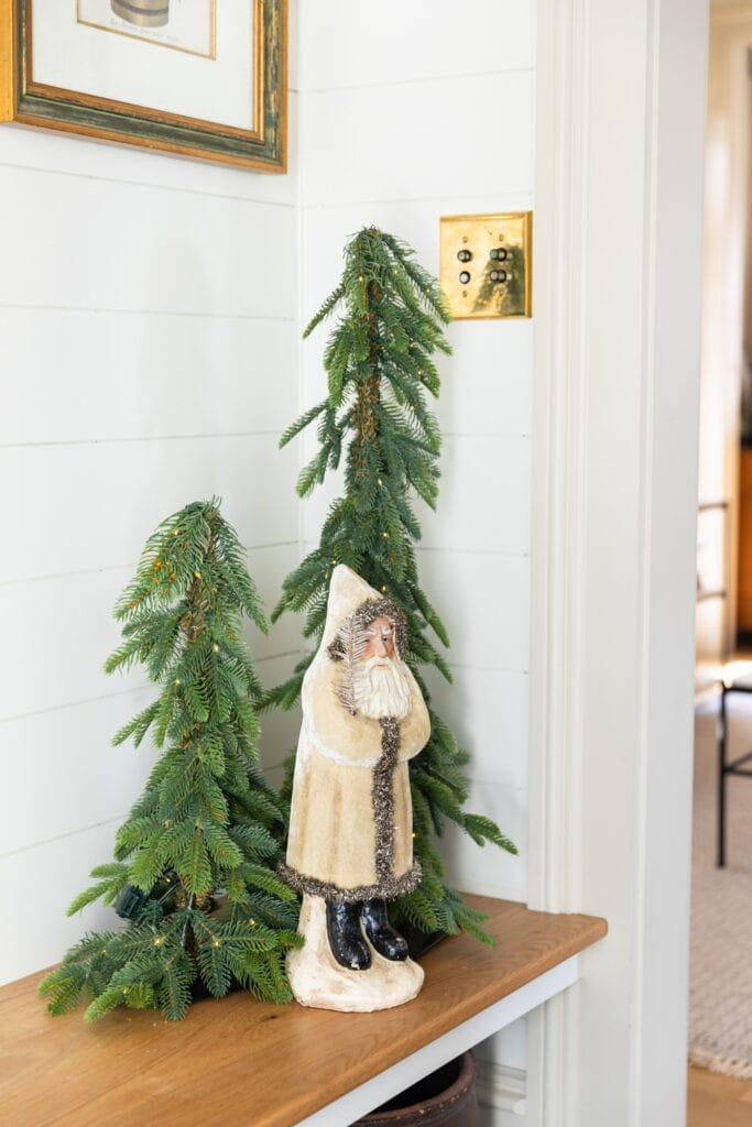 Small white coated toy Santa standing on wooden bench with two green trees with lights right behind