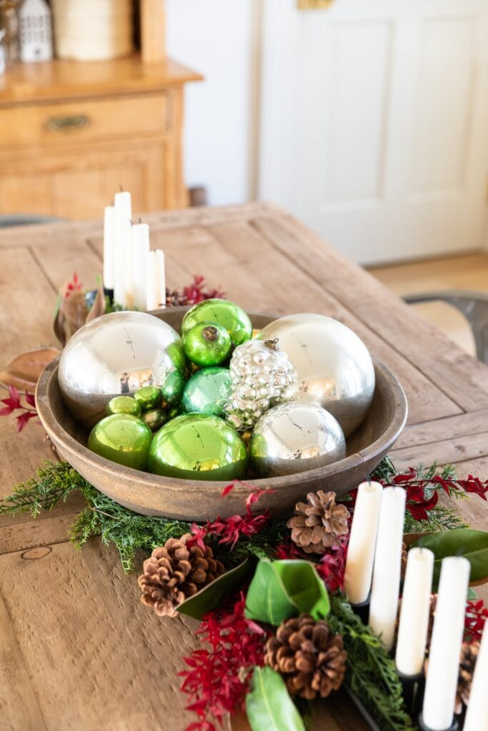 Wooden basket on wooden table filled with green and silver glass Christmas ornaments with greenery and candles all around