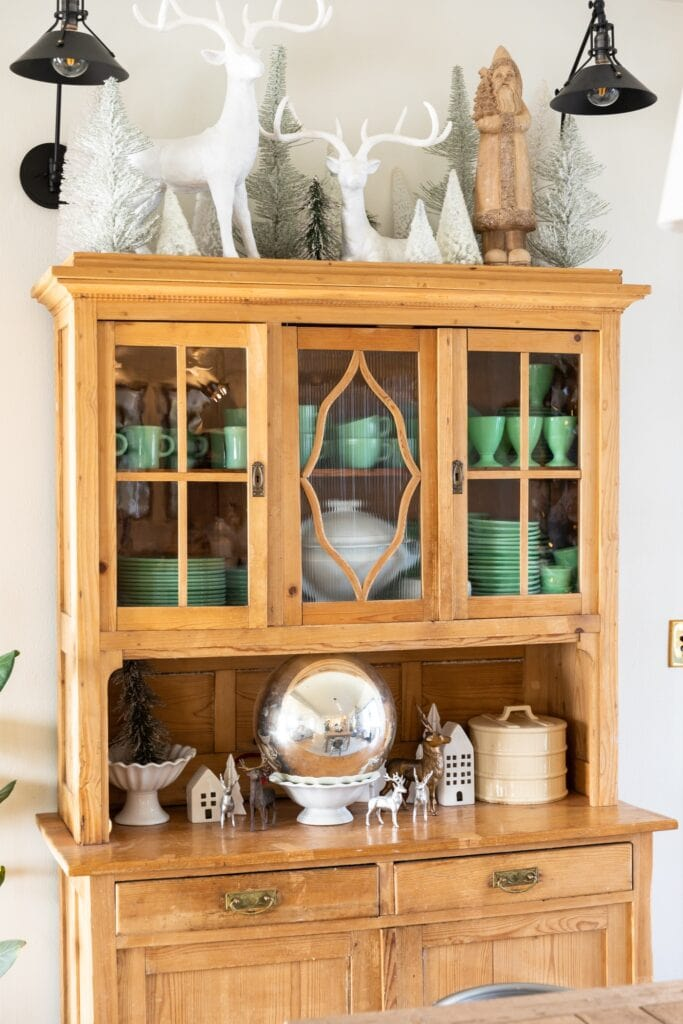 Light pine colored cabinet filled with green mugs and plates topped with white deer and Christmas trees