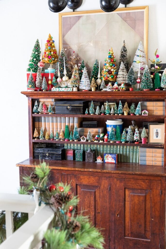 Dark wood cabinet piled with all sizes of Christmas bottle brush trees and small figures with a painting and spot lights above