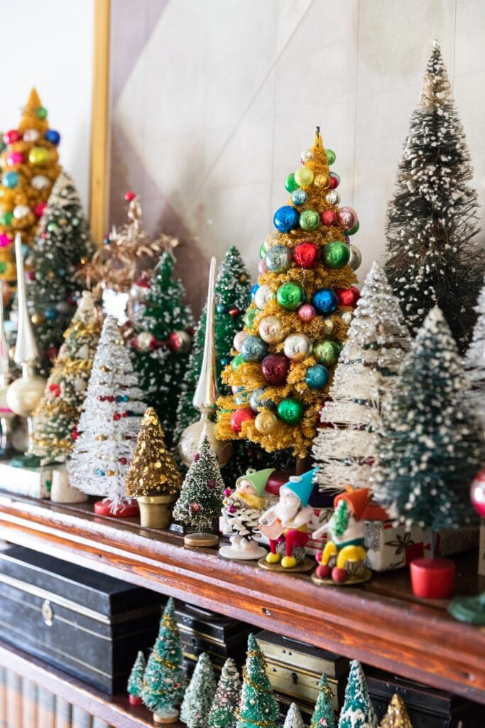 Bottle brush trees of all different shapes and sizes and colors sitting on dark colored wooden shelf