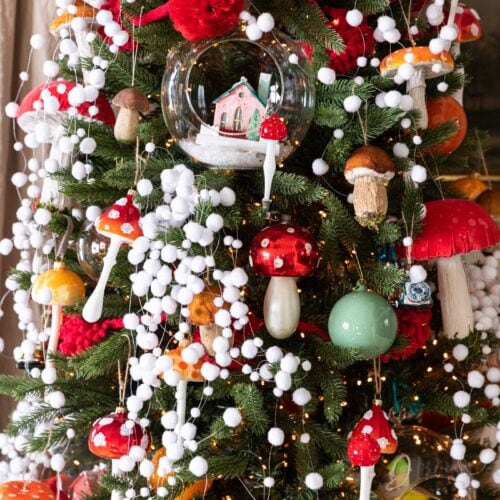 Red colored mushroom ornaments dangling from Christmas tree covered with white fake snow garland