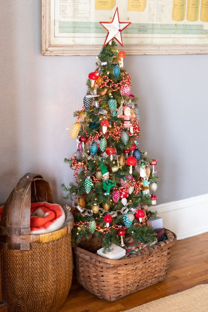 Half size Christmas tree covered with brightly colored vintage glass ornaments sitting in a basket with small vintage boxes piled all around the base