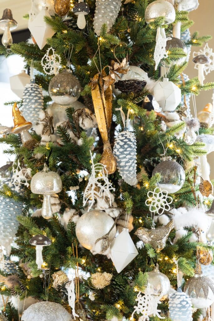 Close up view of gold and silver and white ornaments hanging on tall skinny Christmas tree in front of French doors