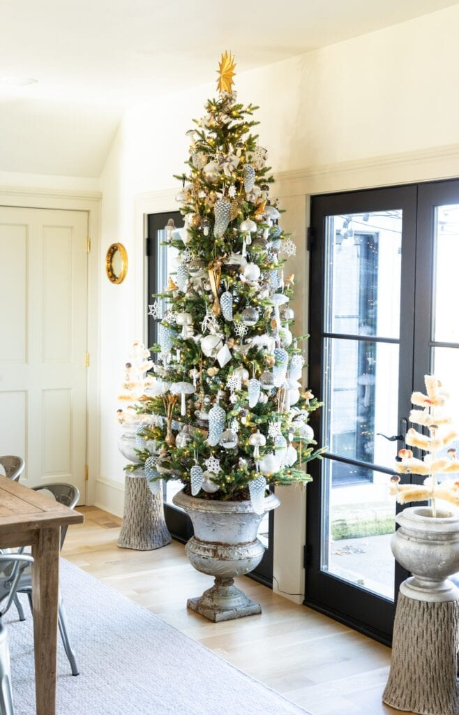 Large Christmas tree in concrete urn sitting in dining room covered in golds and silvers with black French doors behind leading onto patio
