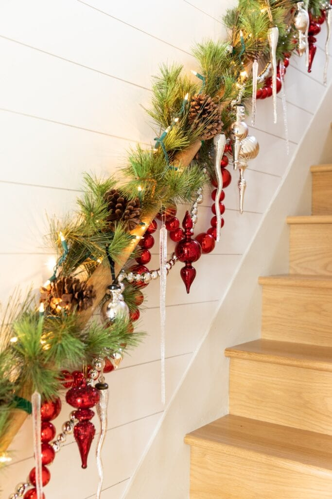 Red and silver ornaments and garland dangling from wood handrail in a stairwell topped with icicles